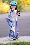 Little girl on skate scooter. A little 4 yr old girl wearing a protective helmet, pads and gloves playing and ready to ride her skate scooter. Shallow depth of Royalty Free Stock Image