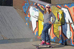 Little girl with skateboard and thumb up Stock Photos