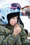 Little girl in ski helmet eats sausage Stock Photos