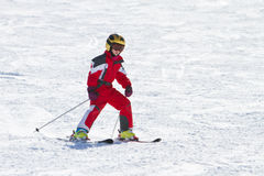 Little girl skiing downhil. On a ski slope Royalty Free Stock Image