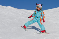 Little girl skiing downhill Stock Photos