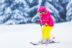 Little girl skiing in the mountains Stock Photos