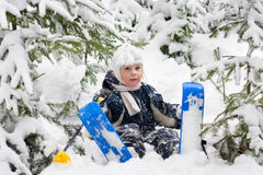 Little girl in skiing sits on the snow Stock Photos