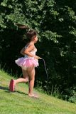 Little Girl Skipping. Little girl wearing a pink net ballet dress, running and skipping on the grass Royalty Free Stock Images