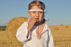 A little girl in slavic traditional ornamented chemise eating rye bread in the harvested filed Royalty Free Stock Photos