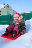 Little Girl on a Sled. A child comes down from a snow hill on a sled Stock Photos