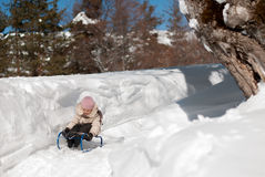 Little girl on a sled sliding down a hill in the snow in winter Stock Image