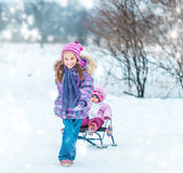 Little girl sledding his sister Stock Photos