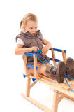 Little girl on sledge in studio Royalty Free Stock Image