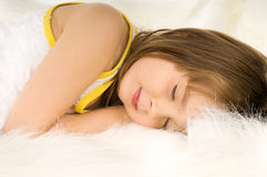 Little girl sleep. The small beautiful girl sleeps, on white to fur Royalty Free Stock Photo