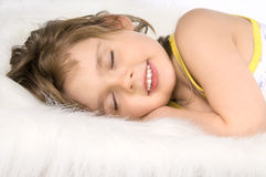 Little girl sleep. The small beautiful girl sleeps and smiles, on white to fur Stock Photo