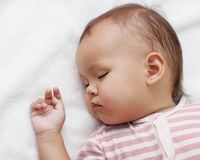 Little girl sleeping. On a white towel Stock Photo