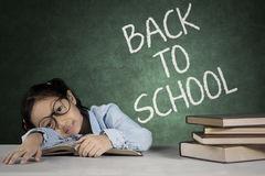 Little girl sleeping above book. Little girl studying in the classroom while sleeping above book with text of back to school on the chalkboard Royalty Free Stock Photography