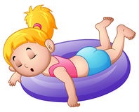 Little girl sleeping above an inflatable ring Royalty Free Stock Images