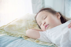 Little girl sleeping on bed. Little Asian girl sleeping on bed at day time Royalty Free Stock Images