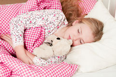 Little girl sleeping in bed. Little cute girl sleeping in bed and hugging teddy bear Royalty Free Stock Image