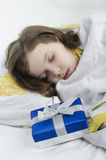 Little girl sleeping in bed with gift Stock Photography