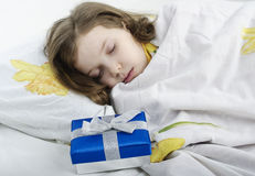 Little girl sleeping in bed with gift Royalty Free Stock Photos