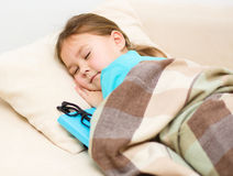 Girl is sleeping with her book and glasses Royalty Free Stock Photo