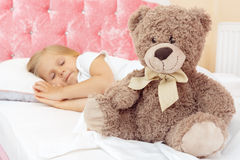 Little girl sleeping in bed with her teddy bear Royalty Free Stock Image