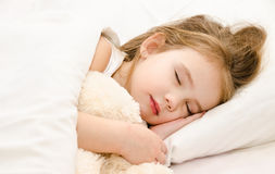 Little girl sleeping in the bed with her toy Royalty Free Stock Photos