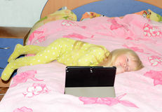 Little Girl Sleeping on Bed with Tablet on Stand Stock Image