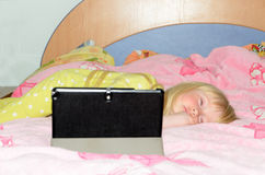 Little Girl Sleeping on Bed with Tablet on Stand Royalty Free Stock Photo