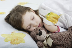 Little girl sleeping in bed with teddy bear Stock Photo