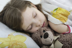 Little girl sleeping in bed with teddy bear Stock Images