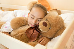 Little girl sleeping on big teddy bear at bed Royalty Free Stock Image