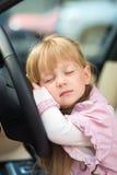 Little girl sleeping on car steering wheel Stock Image