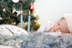 Little girl sleeping in Christmas. Little girl sleeping under the Christmas tree Royalty Free Stock Photo