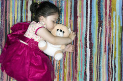 Little girl sleeping on a colorful rug. Little girl sleeping peacefully with her teddy bear on a colorful rug Stock Photos