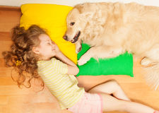 Little girl sleeping on her lovely dog's pillow. Top view of Golden Retriever, protecting it's owner dream, while little girl sleeping on her lovely dog's pillow Royalty Free Stock Images