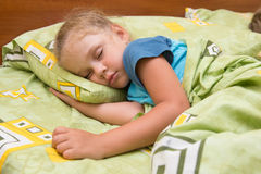 Little girl sleeping on her side in bed with his hand under pillow and covered with a blanket. Little girl sleeping on her side in bed with his hand under the Royalty Free Stock Image