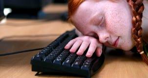 Little girl sleeping on keyboard. In elementary school stock footage