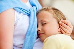 Little girl sleeping on mother lap Stock Image