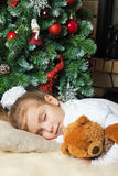 Little girl sleeping near christmas tree Stock Images