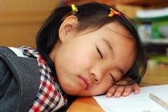 Little girl is sleeping near her homework stock photo