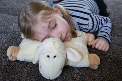Little girl sleeping on a pillow in the shape of sheep. Royalty Free Stock Photo