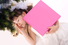 Little girl sleeping under a Christmas tree. Pretty little girl sleeping under a Christmas tree with present Royalty Free Stock Images