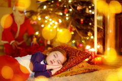 Little girl sleeping under the Christmas tree Stock Image