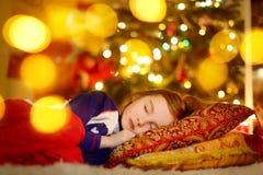 Little girl sleeping under the Christmas tree Royalty Free Stock Image