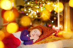 Little girl sleeping under the Christmas tree Stock Image