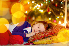 Little girl sleeping under the Christmas tree Stock Photos