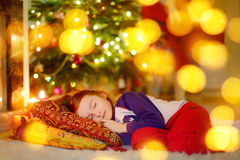 Little girl sleeping under the Christmas tree Royalty Free Stock Photos