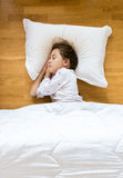Little girl sleeping on wooden floor on white pillow Royalty Free Stock Images