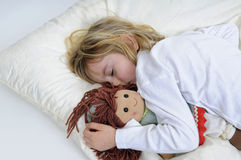 Little girl sleeps. Blond little girl with puppet sleeps in bed stock image