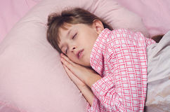 The little girl sleeps in a bed Stock Photos
