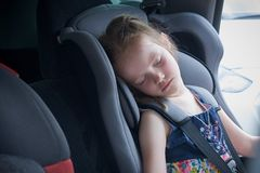 A little girl sleeps in a comfortable car seat for children royalty free stock image